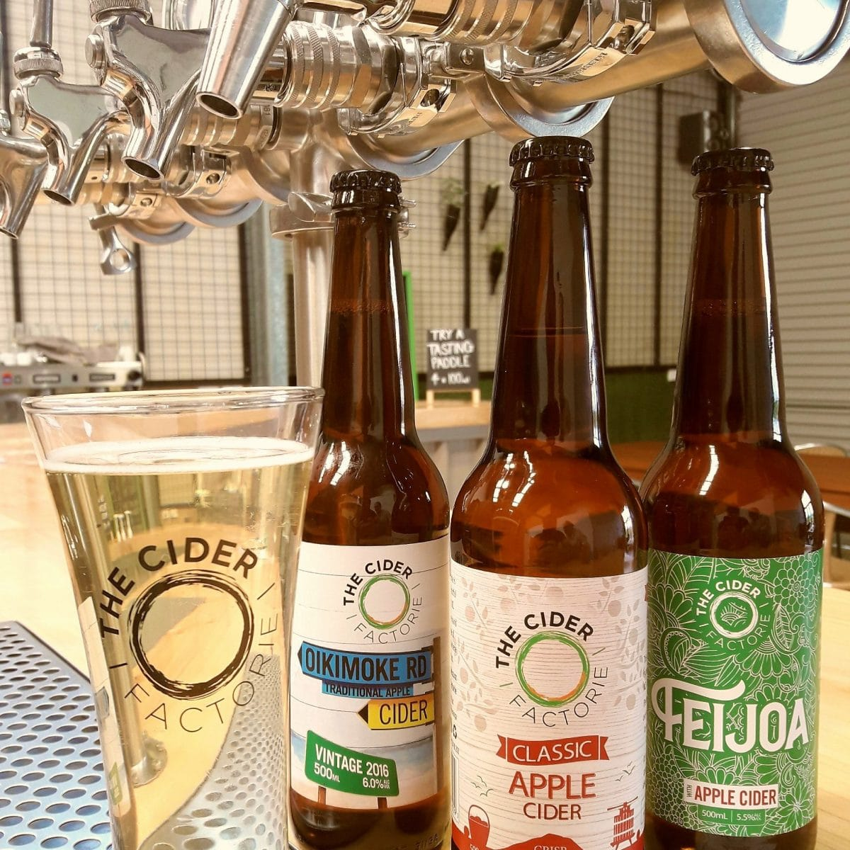 A small selection of our ciders sitting on the top of the bar in front of the bar taps.